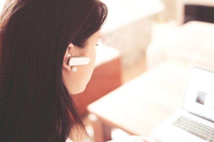 woman-wearing-earpiece-using-white-laptop-computer