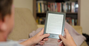A person holding an e-reader called, Kobo, in hand.