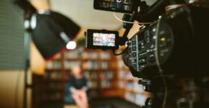 A woman in formal attire seated on a chair being recorded on a video camera.