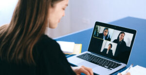 A woman in formal attire seated at her work station attending a video conference.