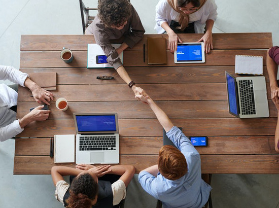 A group of six people sitting around a table with their laptops. Two of them shake hands.